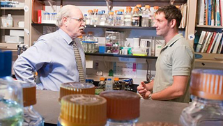 Faculty member talks with visitor to lab