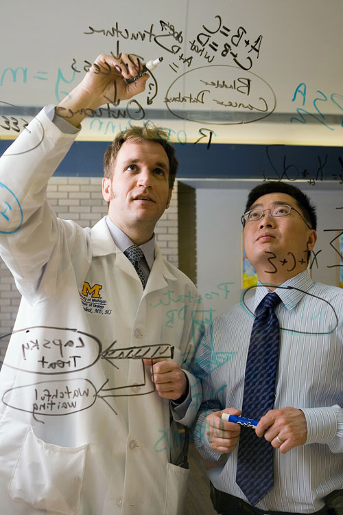 Urology researchers work out a problem on an erasable board