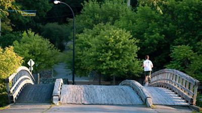 A runner crosses a wooden bridge in Ann Arbor